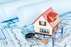 House on packs on a blue print. Stock Images