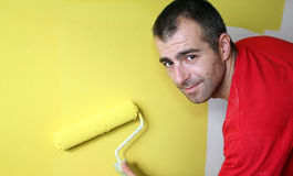 House Painter. Man, painting a wall with yellow paint and a paint roller. Selective focus Royalty Free Stock Photography