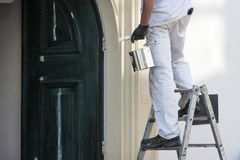 House painter. Close-up of a professional house painter with paint and brush Stock Images