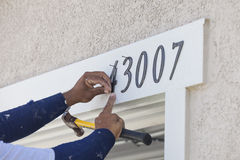 House Painter Contractor Nails Address Numbers to House Facade Royalty Free Stock Images