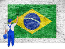 House painter covers brick wall with flag of Brazil Stock Image