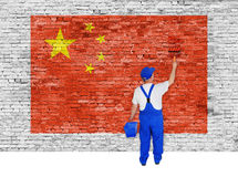 House painter covers brick wall with flag of China Stock Photo