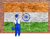 House painter covers brick wall with flag of India Stock Image