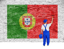 House painter covers brick wall with flag of Portugal Royalty Free Stock Photo