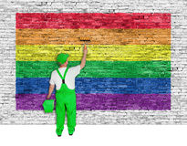 House painter covers brick wall with rainbow flag Stock Photos