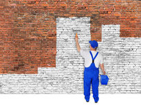 House painter covers brick wall with white paint Stock Photography