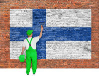 House painter covers wall with flag of Finland. House painter covers brick wall with flag of Finland Stock Photos