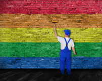 House painter covers wall with rainbow flag Royalty Free Stock Photo