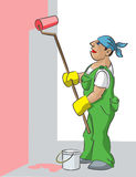 House-painter. The man in a uniform paints with the roller a wall houses in pink color Royalty Free Stock Photo