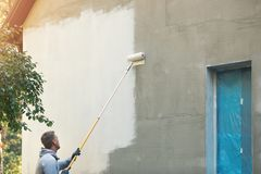 House painter painting building exterior with roller. On high handle Royalty Free Stock Photos