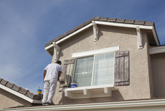 House Painter Painting the Trim And Shutters of Home Royalty Free Stock Photography