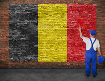 House painter paints flag of Belgium on brick wall. House painter paints flag of Belgium on old brick wall Royalty Free Stock Photography