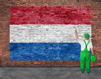 House painter paints flag of Hetherlands on brick wall. House painter paints flag of Hetherlands on old brick wall Royalty Free Stock Photos