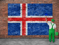 House painter paints flag of Iceland on old brick wall Stock Photo