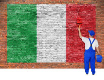House painter paints flag of Italy on brick wall Stock Image