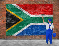 House painter paints flag of Republic of South Africa. On old brick wall Royalty Free Stock Photo