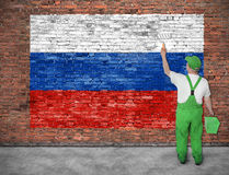 House painter paints flag of Russia. On old brick wall Stock Images