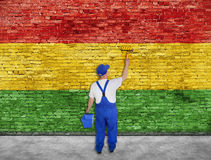 House painter paints Reggae flag on brick wall Royalty Free Stock Photography