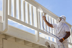 House Painter Spray Painting A Deck of A Home. House Painter Wearing Facial Protection Spray Painting A Deck of A Home Royalty Free Stock Images