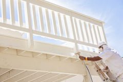 House Painter Spray Painting A Deck of A Home Stock Photos