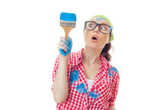House painter woman. Funny surprised woman painter holding paint brush, girl ready for renovating or painting, isolated on white Stock Photo