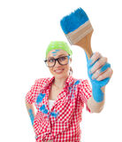 House painter woman. Happy woman with a paint brush holding it out at arms while painting a wall, brush in a focus, isolated on white Royalty Free Stock Images