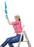 House painter woman. Happy woman sitting on ladder and painting a wall an blue color, isolated on white. House painter female holding paint roller and renovating Stock Image