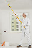 House painter at work with painting roller Stock Image