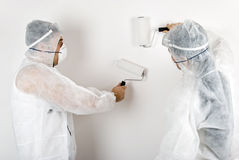 House painters. Two house painters dressed with protective outfit paint white wall.Also,check out Workers and tools Stock Images
