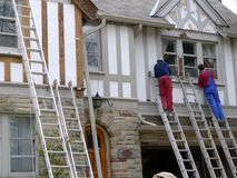 House painters at work. Springtime is a popular time for outdoor home repairs.  These painters are stripping the old paint off the wooden slats on the front of Stock Images