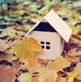 House from paper in bright yellow autumn leaves. Royalty Free Stock Image
