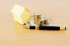 House paper with money coins stack and Business Fountain Pen for Royalty Free Stock Photography