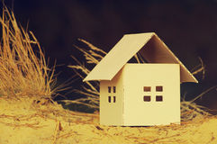 House from paper on sand. Concept image house. Stock Images