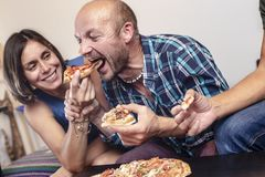 House party. Friends eating and having fun. Man playfully takes a slice of pizza at the woman royalty free stock photo