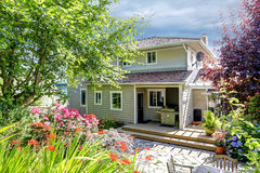 House with patio area and garden. House with walkout deck and patio area surrounded by garden royalty free stock photography