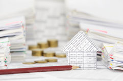 House and pencil with blur coins between overload of paperwork Royalty Free Stock Images