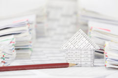 House with pencil between blur overload of paperwork Royalty Free Stock Photo