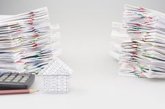 House with pencil and calculator with dual pile overload document Royalty Free Stock Photos