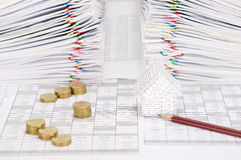 House and pencil with coins have dual document as background. House and pencil with step pile of gold coins on finance account have dual pile overload document Stock Photography