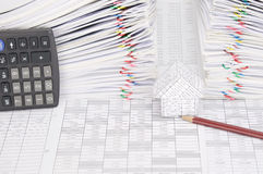 House and pencil have dual overload document as background. House and pencil on finance account have calculator place vertical and dual pile overload document of Royalty Free Stock Image