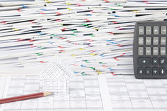 House with pencil and overload of confused paperwork as background Royalty Free Stock Photo