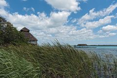 House and pier on the shore of the lagoon of Bacalar, Quintana Roo, Mexico.  Royalty Free Stock Photography