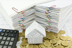 House on pile of gold coin with calculator Royalty Free Stock Photo
