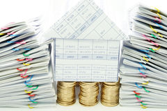 House on pile of gold coins between dual pile overload. Document with colorful paperclip on white background Stock Photography