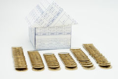 House and pile of gold coins. Have blur on white background Royalty Free Stock Photo