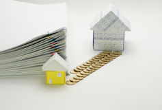 House and pile of gold coins. With little house and pile overload paperwork of report with colorful paperclip have blur on white background Royalty Free Stock Photography