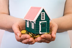 House on a pile of money in woman hands Royalty Free Stock Image