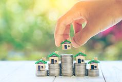 House placed on coins Men`s hand is planning savings money of coins to buy a home concept concept for property ladder, mortgage a. Nd real estate investment stock photo