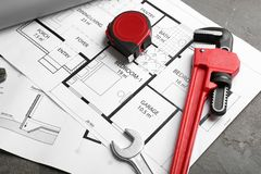 House plan with plumber`s tools. On grey table stock images