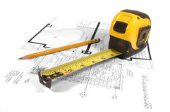 House Planning. A measuring tape and a pencil on a floor plan blue print Royalty Free Stock Photo